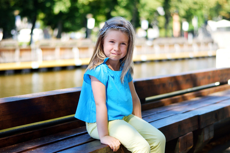 Adorable little girl playing by a river in sunny park on summer day