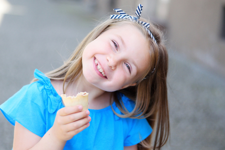 Adorable little girl eating tasty ice cream at park on sunny summer day