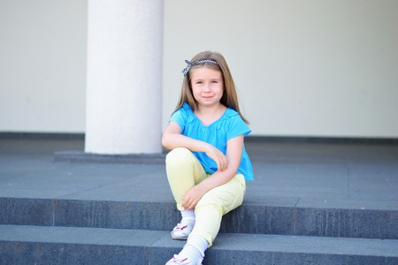 Adorable little beautiful girl sitting on a stairway outdoor