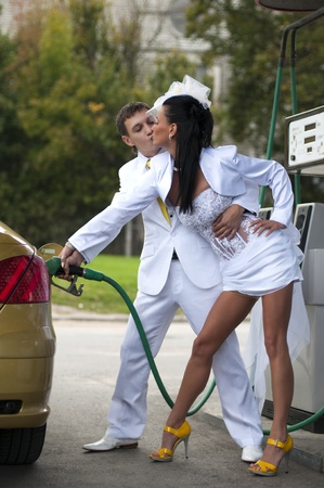 bride and groom kissing at fuel station photo