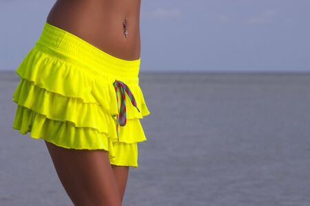 sexy tanned torso in yellow skirt Stock Photo