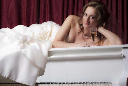 Beautiful bride on a white piano photo