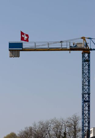 yellow industrial big crane with Switzerland flag, with space for logo and texts