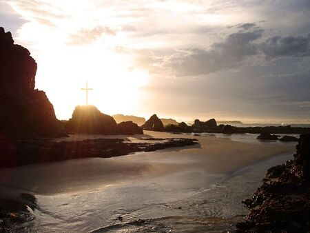 easter sunrise: Rays of light pass through a crucifix on a rocky coastline