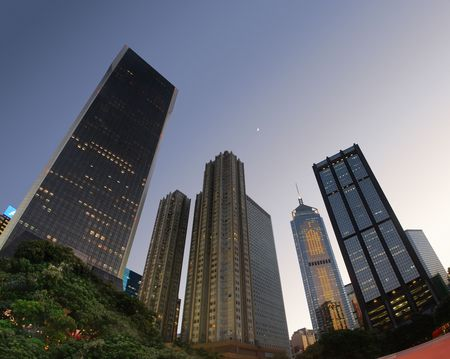 wan: Skyscraper buildings of Hong Kong Wan Chai as the sun sets and moon rises in early evening.