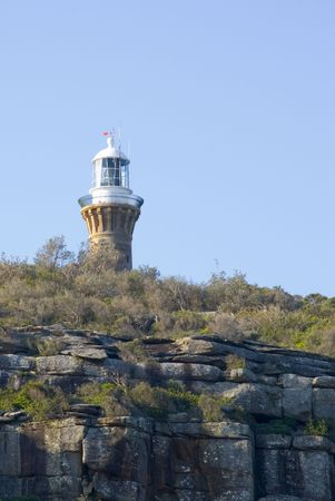 A lighthouse upon a cliff with a perfect blue sky for copyspace. Historic Barrenjoey Lighthouse at Palm Beach, Sydney, New South Wales, Australia photo
