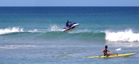 jetskier sauts de vague de surf en l'air tandis que le kayakiste porte sur