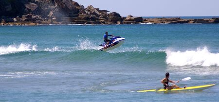 jetski: jetskier jumps out of surf wave into air while kayaker looks on. - exciting extreme jetski stunt Stock Photo