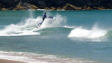 daredevil: A jetskier jumps a wave off a beach sending alot of spray and foam into the air Stock Photo