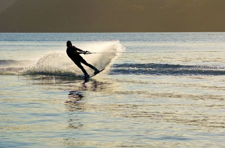 waterskiing: At sunset a Waterskier sprays water into air as he changes direction, on Pittwater, New South Wales, Australia