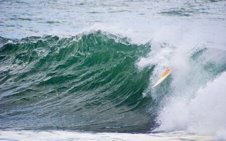 dumped: surfer dumped in big wave. Only surf board still surfing the wave