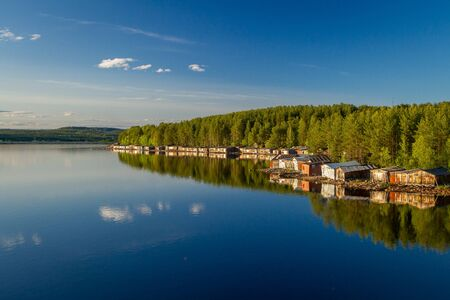 Old wooden boat sheds on Lake Kovdozero in the Murmansk region, Zelenoborsky village. The reflection in the water of trees and boat garages