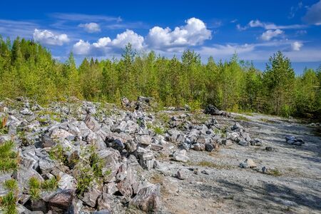Marble rock with cracks. On the marble white and gray stains. The forest around. Ruskeala, Karelia. Stock Photo
