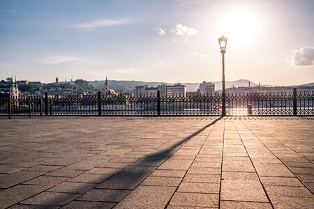 Sunset. Reflection of a lantern on the sidewalk. Danube Embankment in Budapest