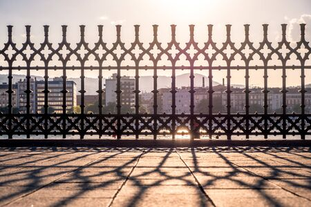 Sunset. Reflection of the lattice fencing. Danube Embankment in Budapest