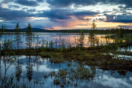 Summer Night landscape in the north of the Kola Peninsula in Russia. White nights, lakes, forests and beautiful clouds reflected in the water Stock Photo
