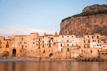 Seafront of Tyrrhenian Sea and Medieval houses of Sicilian coastal medieval city Cefalu in sunset