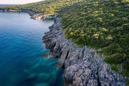 Aerial view of Trsteno beach in Montenegro, near Budva, in a beautiful bay with a rocky shore, blue water