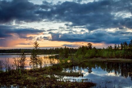 Summer Night landscape in the north of the Kola Peninsula in Russia. White nights, lakes, forests and beautiful clouds reflected in the water