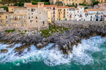 Aerial view of the rocky coast and the houses of Cefalu from the sea in windy and stormy weather. Big waves beat against stones. Sicily, Italy