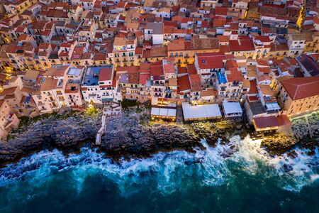 Aerial view of the rocky coast and the houses of Cefalu from the sea in windy and stormy weather. Big waves beat against stones. Streets with the city lights. Italy, Tyrrhenian SeaSicily, Italy Imagens