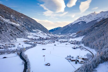 Winter morning cityscape in the Austrian town of Neustift. Aerial view of the alps mountains valley. Tyrol, Stubai