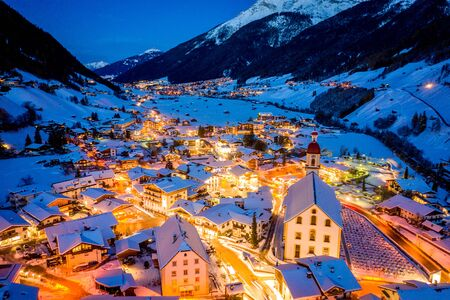 Winter night cityscape in the Austrian town of Neustift. Aerial view of the town center and the church. Night illumination of houses and traffic light. Tyrol, Stubai Valley