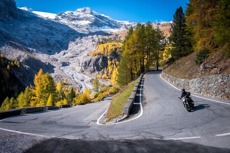 Dolomites Mountains, autumn landscape in the Passo Stelvio valley in South Tyrol in the Stelvio National Park, Alps, northern Italy, Europe. Mountain road with bike