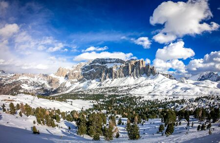 Landscape at a ski resort Campitello di Fassa Italy. Winter Dolomites and blue sky with clouds.
