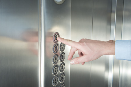 elevator: Human hand pressing the last floor button in the elevator