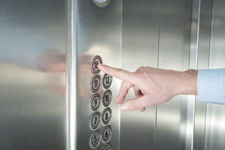 tablero de control: La mano del hombre presionando el botón del último piso en el ascensor