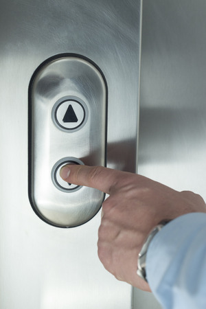 businessman waiting call: Person pushing down arrow elevator button