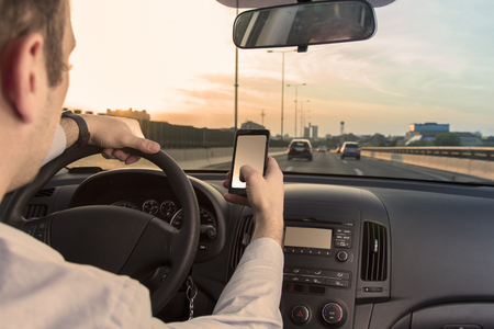 Man using cell phone while driving the car Reklamní fotografie