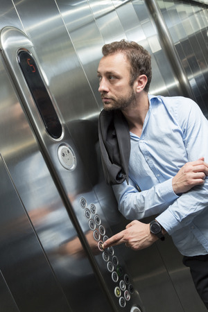 Businessman pressing the floor button in the elevator 版權商用圖片