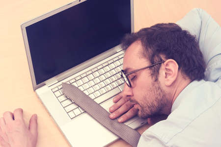 working lifestyle: Businessman sleeping on laptop with his tie over keyboard