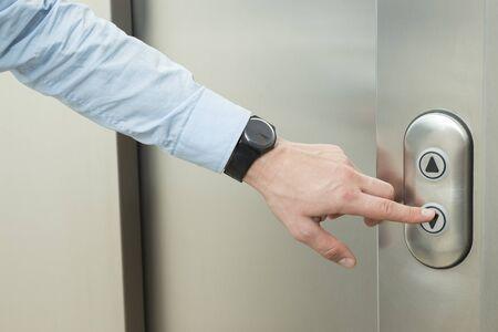 empujando: Persona que empuja hacia abajo el bot�n del ascensor flecha