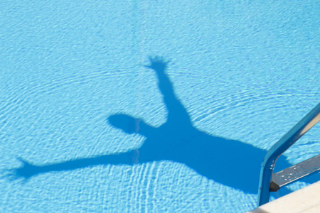 Man shadow with arms raised in the swimming pool