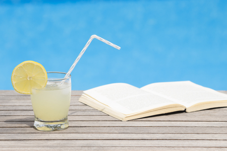 Glass of iced lemonade and opened book on the table - poolside 版權商用圖片