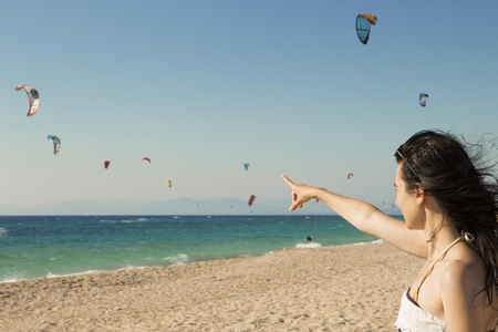 Young woman points the finger at kitesurfing kites on the beach Stock Photo