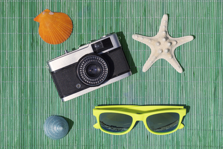 Starfish, retro camera, gaudy yellow sunglasses, blue sea snail and orange sea shell on green bamboo straw mat as summer vacation symbols. Top down view.