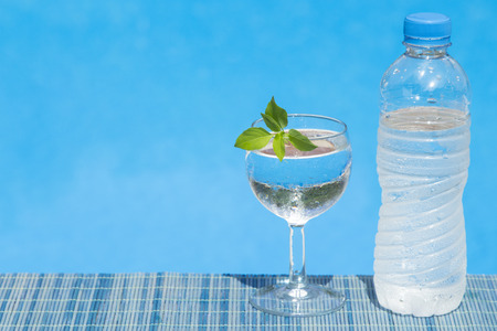 Glass of water with leaf decoration and bottle of water placed on bamboo straw mat. Swimming pool water surface in the background.