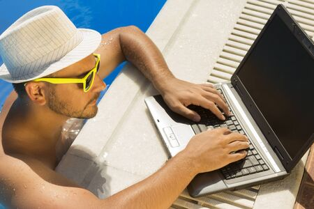 Man in the swimming pool with hand on laptop keyboard. He is wearing hat and sunglasses.  Stock Photo
