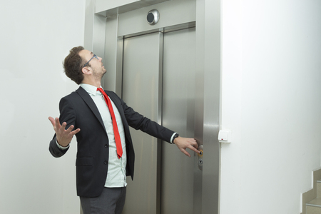 Businessman pressing the elevator up button and looking the elevator display that indicates that elevator stopped working.    Standard-Bild