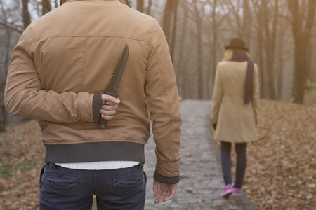 Maniac holding a knife behind his back and waiting for innocent girl to get closer    Banque d'images
