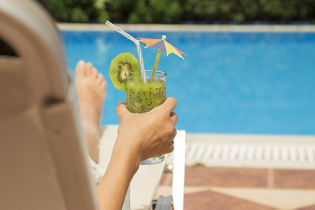 Woman enjoying the vacation in resort next to the swimming pool. She is holding a fresh smoothie of kiwi juice.