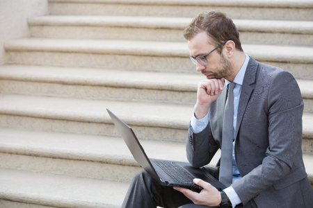 Young professional sitting on the steps with the laptop on his knees outdoors. Businessman is looking at laptop screen and thinking about the next strategic moves.