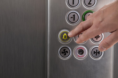 Man pressing the alarm button in the elevator with his finger