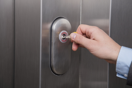 Person unlocking the emergency lock on the elevator Banco de Imagens - 96610558