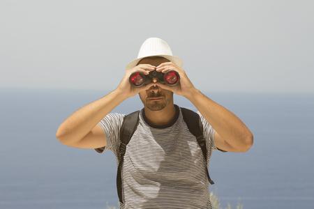 Backpacker in stripped shirt looking through binoculars. Ocean in the background.