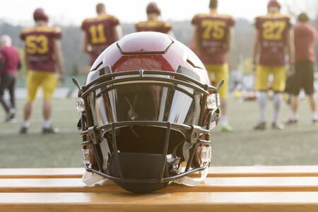 Football helmet on the bench and players behind  스톡 콘텐츠